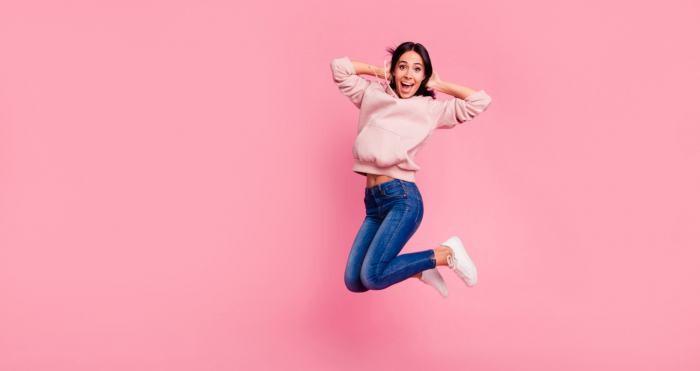 Dunkelhaarige Frau springt vor rosafarbenem Hintergrund  in die Luft.