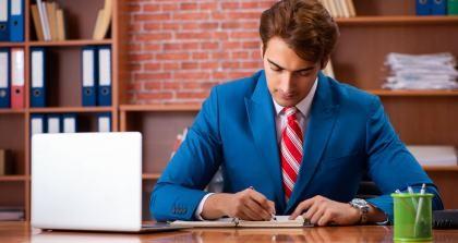 Junger Mann sitzt am Schreibtisch und schreibt.