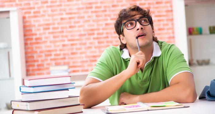 Junger Mann sitzt am Schreibtisch und überlegt.