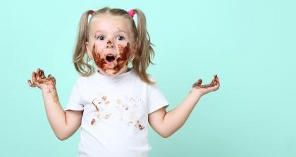 Ein kleines Kind mit Schokolade um den Mund und an den Fingern zuckt ratlos die Achseln.