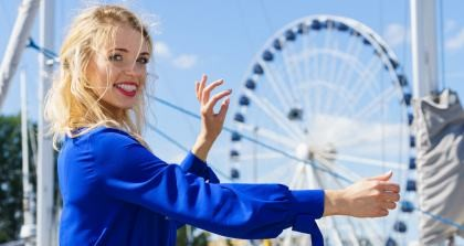 Lächelnde Frau steht vor Riesenrad und misst es mit ihren Fingern. Ein großes Riesenrad ist ein Pleonasmus.