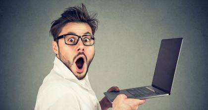 Ein Mann hält einen Laptop und sieht schockiert und verzweifelt über die Word Autokorrektur in die Kamera.