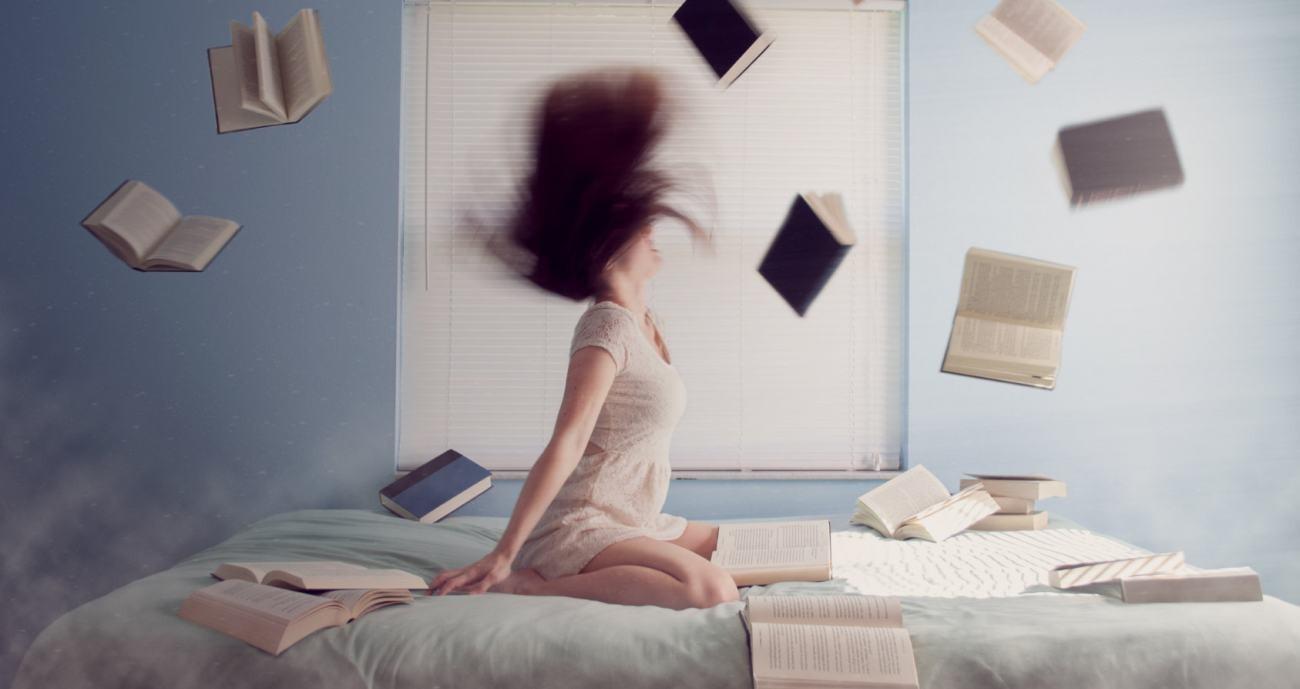 Eine Frau ist auf einem Bett von einem Sturm aus Büchern umgeben