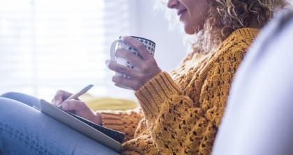 Eine Frau mit einer Tasse in der Hand schreibt sich gesund.