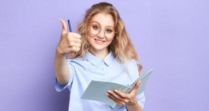 Eine junge Autorin mit Notizheft hebt den Daumen für jetzt wieder mögliche Textaufträge
