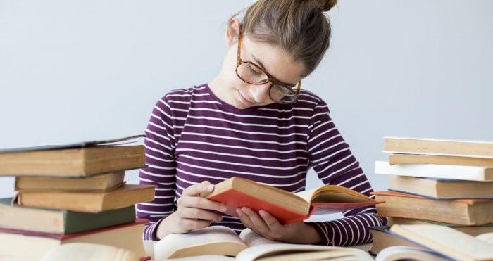 Die beste Hilfe für Autoren in der Corona-Krise ist das Hamstern von Büchern. Eine junge Leserin in einem Berg aus Büchern macht es vor.