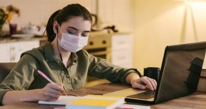 Eine junge Frau schreibt Texte in der Coronakrise im Homeoffice.