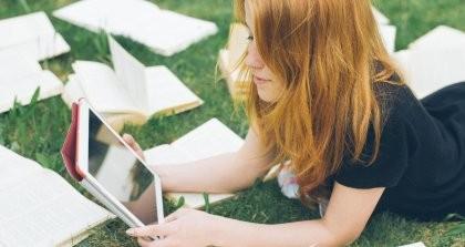 Eine Frau liest auf einem E-Reader von Printmedien umgeben.