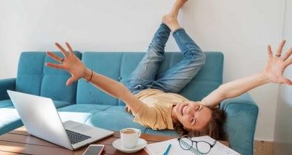 Eine Autorin liegt auf dem Sofa vor ihrem Laptop mit Kaffee, Handy und Brille und freut sich über die neuen digitalen Möglichkeiten im Literaturbereich.