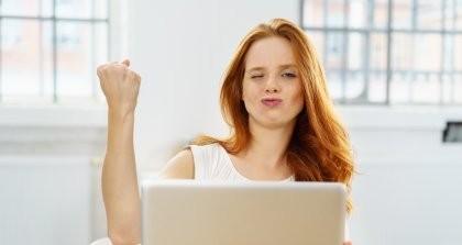Eine Werbetexterin sitzt an ihrem Laptop und freut sich über ihren Erfolg mit der Anzeige des Jahres.