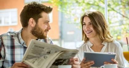 Ein Mann mit einer Zeitung und eine Frau mit einem Tablet lesen die neuesten Nachrichten.
