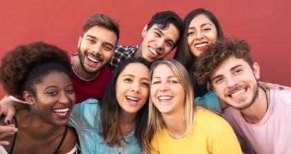 Eine Gruppe von Freund*innen liegt sich in den Armen und lächelt in die Kamera.