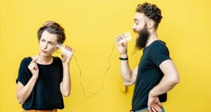 Zwei Menschen kommunizieren über Pappbecher mit einer Schnur daran.