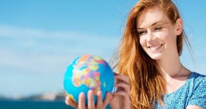 Eine Frau hält einen Globus in der Hand und lächelt.