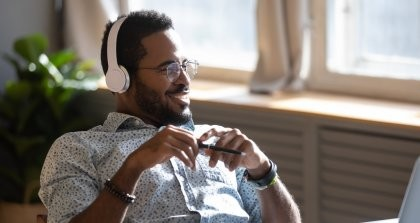 Ein Autor sitzt zurückgelehnt auf seinem Schreibtischstuhl und hört mit Kopfhörern einen Schreibpodcast.