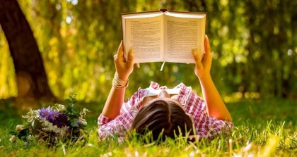 Eine Person liegt im Gras und liest ein Buch.