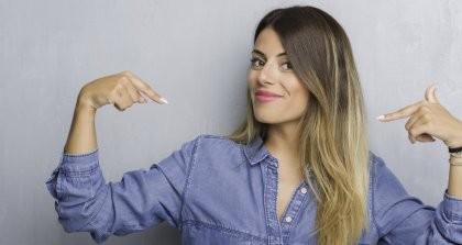 Eine junge Frau zeigt selbstbewusst mit beiden Fingern auf sich selbst.