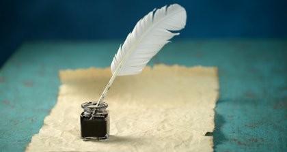 Feder getunkt in schwarze Tinte auf einem Blatt Papier