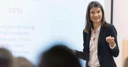 Junge Frau im Anzug hält einen Vortrag